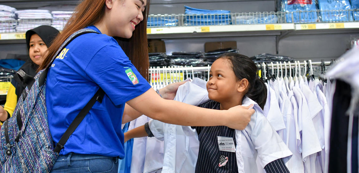 A volunteer helping a child in a store.