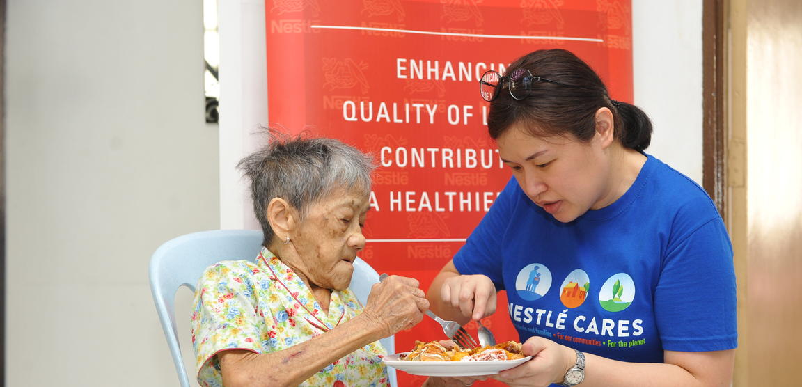 A volunteer helping an elderly lady with her meal.