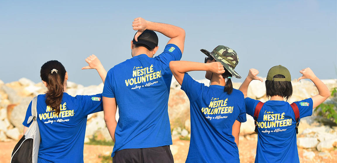 A group of volunteers pointing to the back of their shirts.