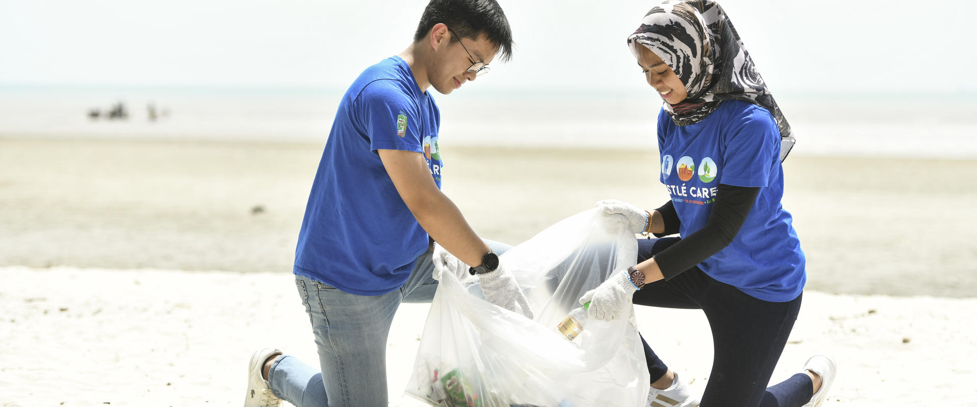 Two volunteers cleaning the beach.